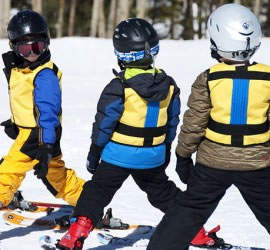 four-children-skiing-in-Kinderlift-vests